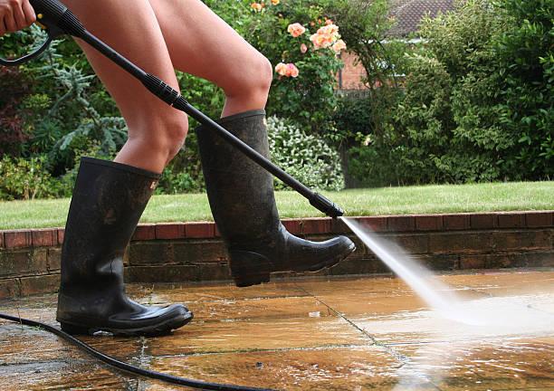 Jeune femme en bottes en caoutchouc qui lave sa terrasse avec un nettoyeur haute pression