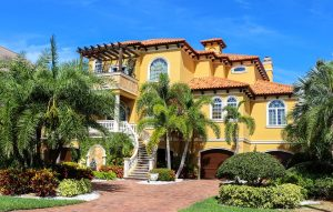 Grande maison jaune avec jardin et palmiers
