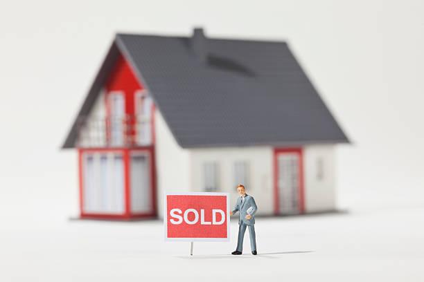 """Maquette d'une maison avec un panneau """"sold"""", soit """"vendue"""""""