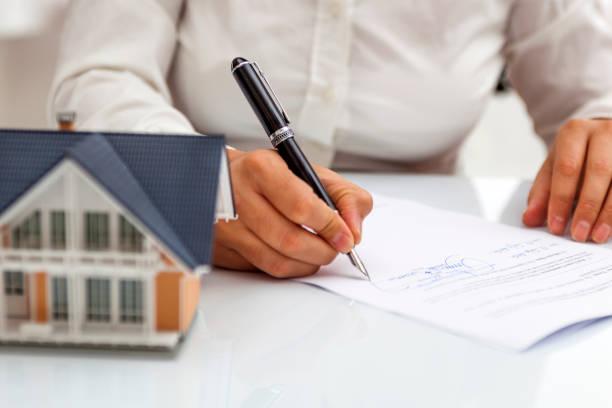 Une personne qui signe un contrat, avec une maquette de maison posée sur le bureau